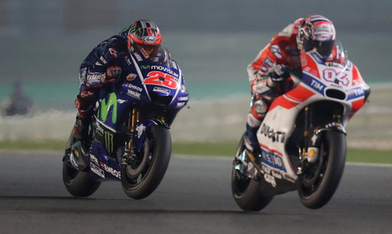 Andrea Dovizioso vs Maverick Vinales. / AFP PHOTO / Karim JAAFAR